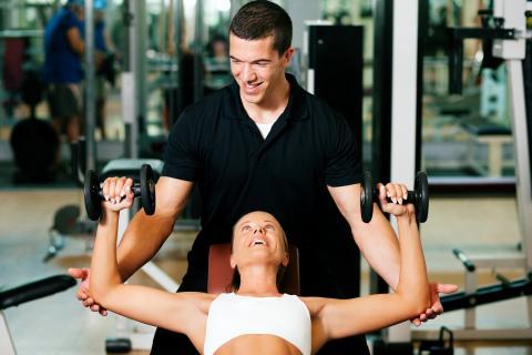 Man spotting a woman doing a bench press